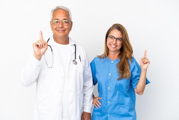 Arts en verpleegster van middelbare leeftijd geïsoleerd op een witte achtergrond die een vinger toont en optilt in teken van het beste