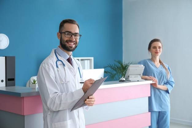 Arts en vrouwelijke receptioniste dichtbij bureau in kliniek