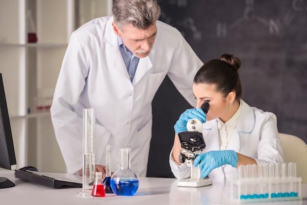Arts en zijn afgestudeerde student werken aan een stof.