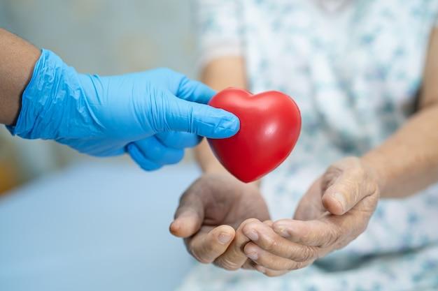 Arts geeft rood hart aan aziatische hogere vrouwenpatiënt.