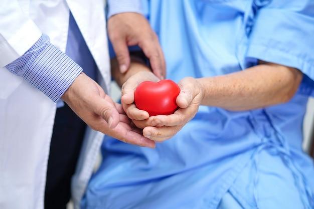 Arts geeft rood hart aan aziatische senior vrouw patiënt.