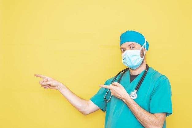 Arts gekleed als chirurg in groen met stethoscoop en masker op gele achtergrond met gebaar dat naar een richting wijst.