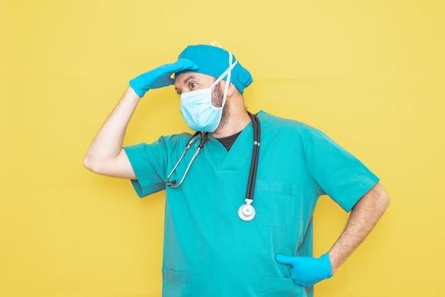 Arts gekleed als chirurg in het groen met een stethoscoop en masker op een gele achtergrond met een bezorgde uitdrukking.