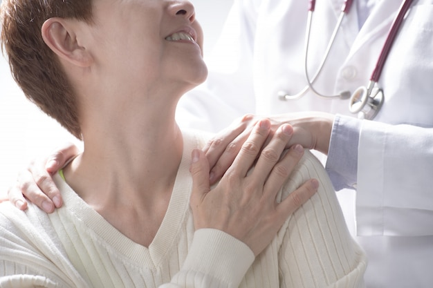 Arts geruststellend senior patiënt en een hand op de schouder van de patiënt te leggen