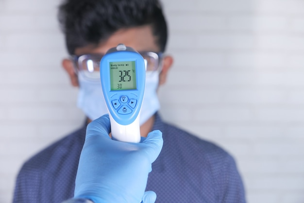 Arts hand met thermometer temperatuur van een man te controleren