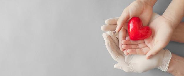 Arts handen met medische handschoenen met kind handen en rood hart, ziektekostenverzekering en orgaandonatie concept
