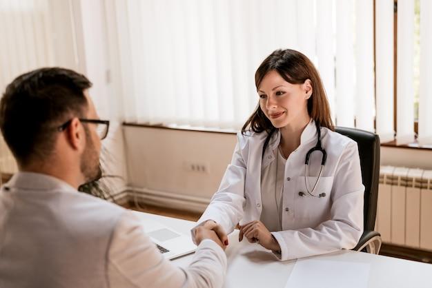Arts handen schudden aan de mannelijke patiënt op kantoor