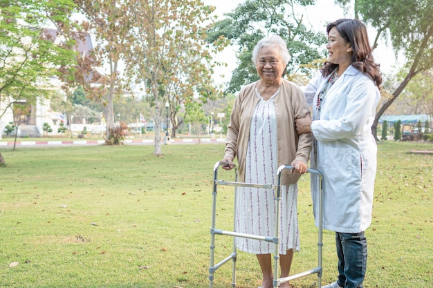 Arts helpt aziatische senior vrouw rollator gebruiken in het park.