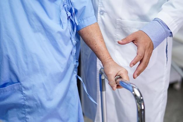 Arts helpt en geeft senior vrouw die rollator in het ziekenhuis gebruikt