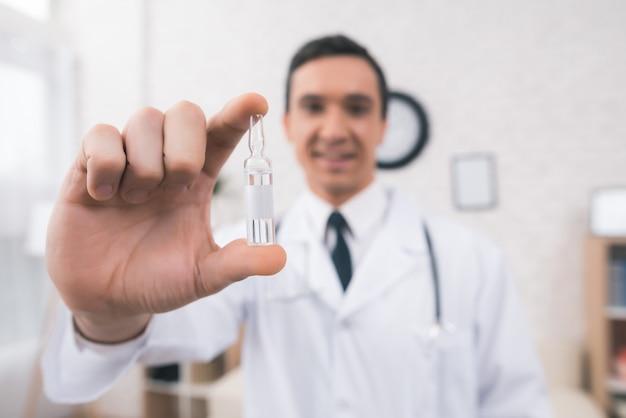 Arts houdt een ampul in de kliniek.