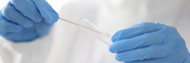 Arts houdt reageerbuis en wattenstaafje in zijn handen met medische handschoenen in laboratorium close-up