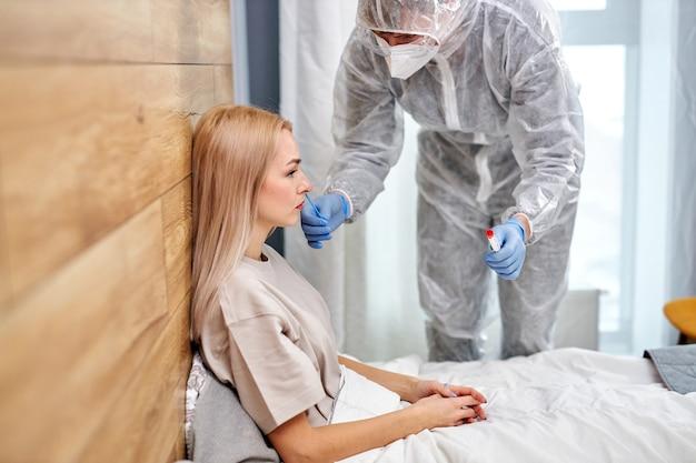 Arts in beschermend pak neemt wattenstaafje uit neus van zieke vrouwelijke patiënt thuis, liggend op bed. laboratoriumtests voor coronavirus covid-19-concept. zijaanzicht op trieste vrouw