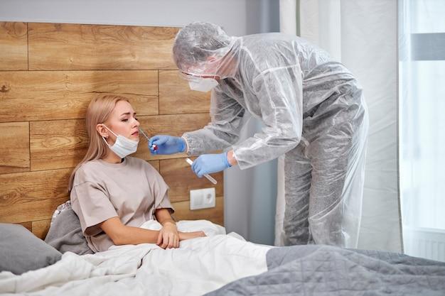 Arts in beschermend pak neemt wattenstaafje uit neus van zieke vrouwelijke patiënt thuis, liggend op bed. laboratoriumtests voor coronavirus covid-19-concept.