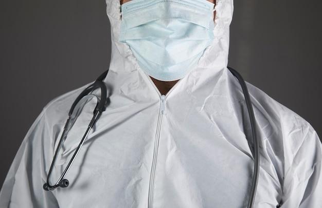 Arts in beschermend uniform en met een stethoscoop op een grijze scène