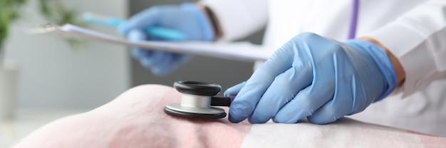 Arts in beschermende handschoenen luisteren naar de hartslag van de patiënt met stethoscoop close-up ziekten