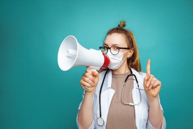 Arts in beschermende kleding met megafoon die mensen aanspoort om thuis te blijven.