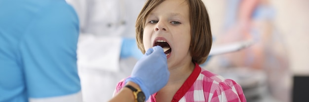 Arts in blauw pak kijkt naar de keel van het kind met een houten stok.