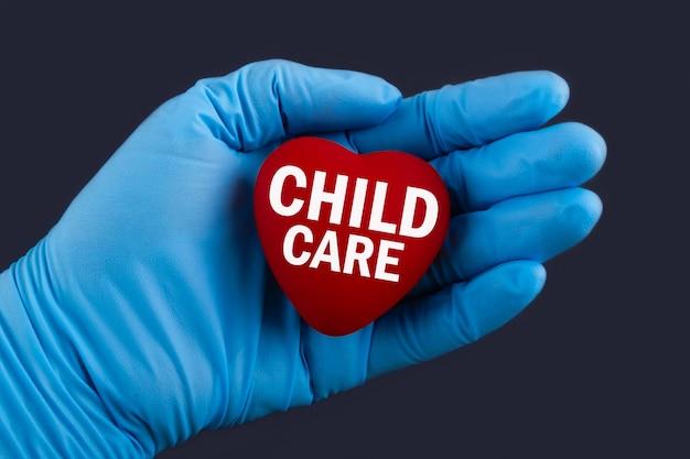 Arts in blauwe handschoenen houdt een hart met tekst kinderopvang, concept