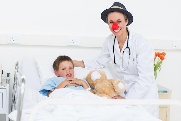Arts in clownkostuum met jongen in het ziekenhuis