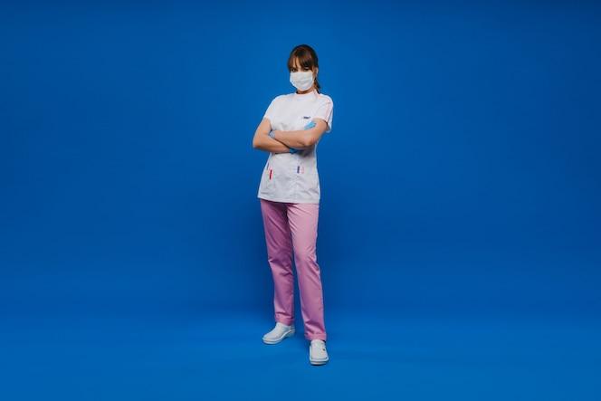arts in een beschermend masker en rubberen handschoenen op een blauwe achtergrond