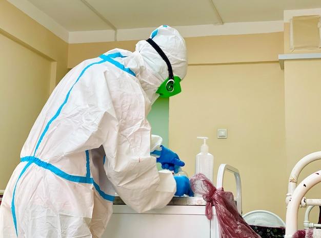 Arts in een beschermend medisch pakmasker werkt in een laboratorium met analyses van covid-patiënten