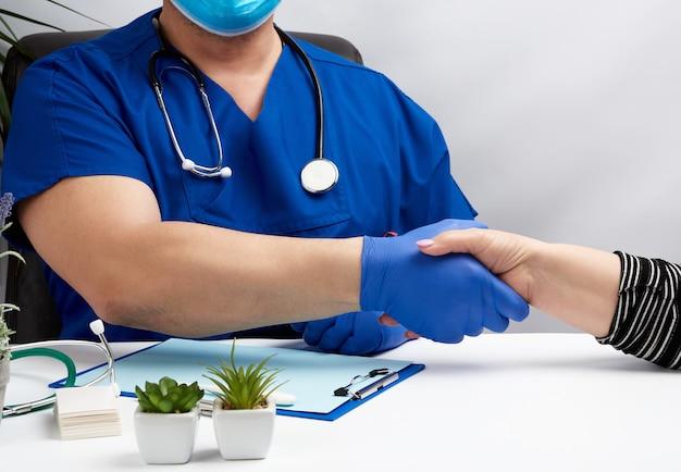 Arts in een blauw uniform zit aan een bureau in een fauteuil en schudt de hand met een vrouwelijke patiënt