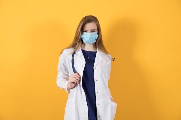 Arts in een chirurgisch pak, witte jas en medisch gezichtsmasker op een gele achtergrond