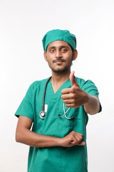 Arts in een chirurgische jurk met een stethoscoop en duimen opdagen op witte achtergrond.