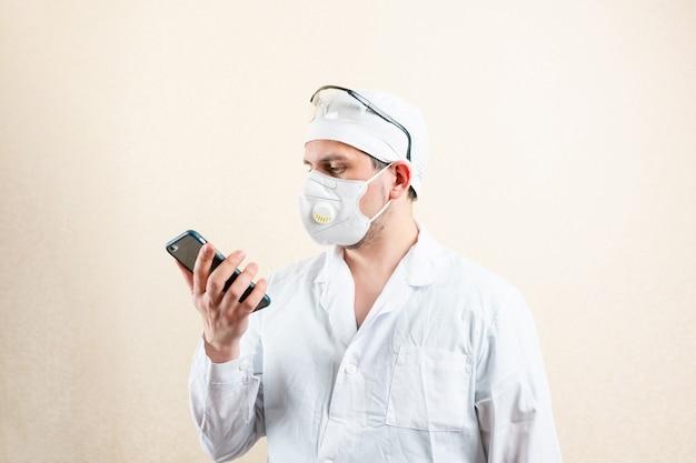 Arts in een masker en bril met een mobiele telefoon. hoge kwaliteit foto