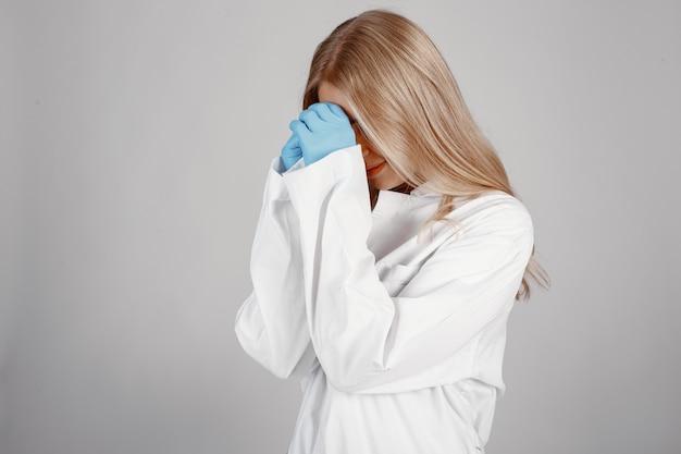 Arts in een medisch masker. coronavirus-thema. ge oleerd over witte muur. bid voor doktoren.