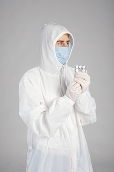 Arts in een medisch masker. coronavirus-thema. geïsoleerd op witte achtergrond. vrouw met pillen.