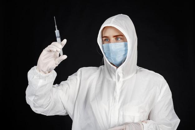 Arts in een medisch masker. coronavirus-thema. geïsoleerd over zwarte muur. vrouw in een beschermend pak.