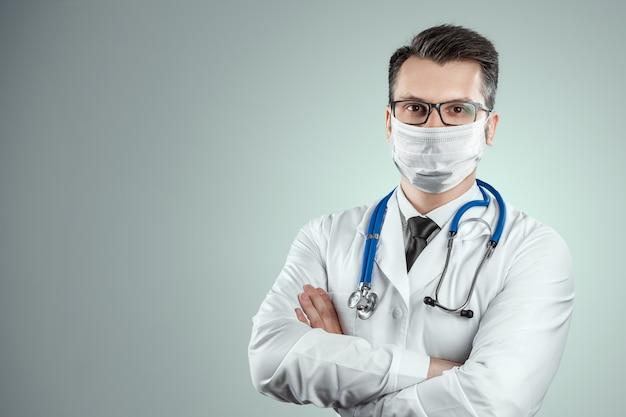 Arts in een medisch masker op een lichte muur. het concept van een verbod om het huis te verlaten, zelfisolatie, quarantaine, voorzorgsmaatregelen, afstand, covid-19.