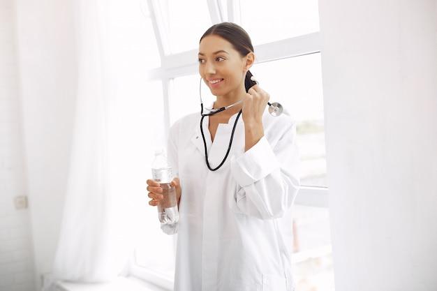 Arts in een uniform die zich op wit bevindt