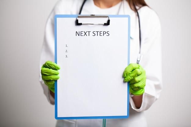 Arts in een witte jas heeft een brief met tekst volgende stappen
