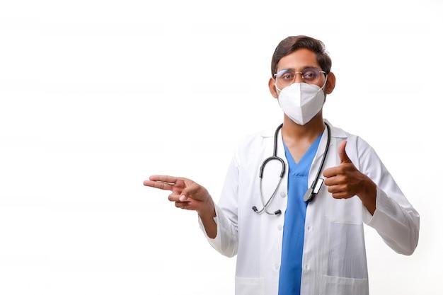 Arts in een witte jas met een stethoscoop en duimen opdagen op witte achtergrond.