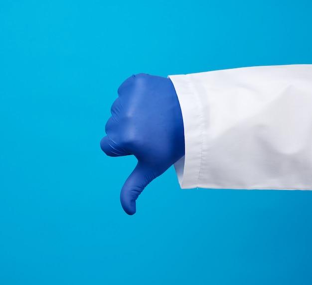 Arts in een witte jas met knopen toont een gebaar van afkeer met zijn hand