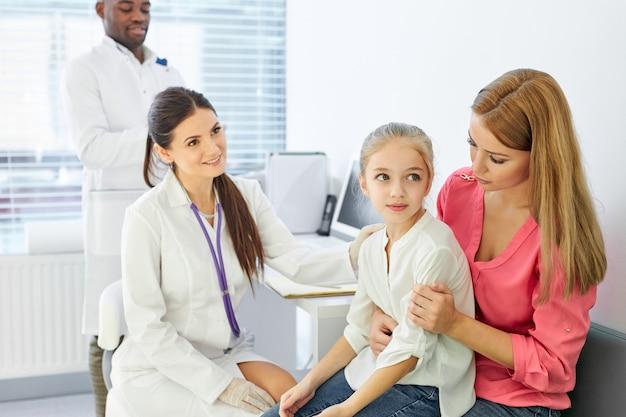 Arts in gesprek met kind en zijn moeder tijdens gezondheidscontrole in de kliniek, moeder en meisje krijgen consultatie van professionele kinderarts of huisarts tijdens bezoek aan het ziekenhuis