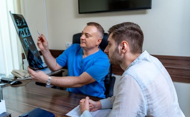 Arts in gesprek met mannelijke patiënt op kantoor. x-ray uitleggen aan een pateint.