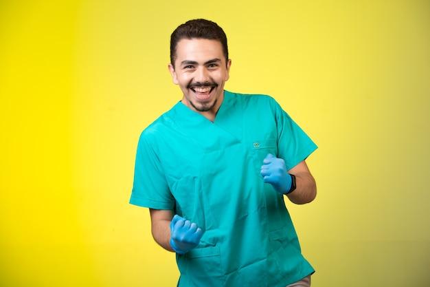 Arts in groen uniform en handmasker dat en zijn geluk op geel glimlacht toont.