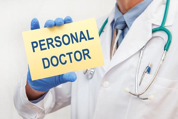 Arts in handschoenen met een bordje met de tekst - persoonlijke arts