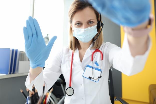 Arts in masker en handschoenen die patiënt begroeten bij beeldscherm. remote medisch consult concept