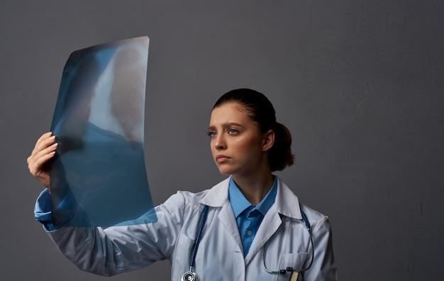 Arts in medische jurk met x-ray op grijze achtergrondonderzoek in laboratorium. hoge kwaliteit foto
