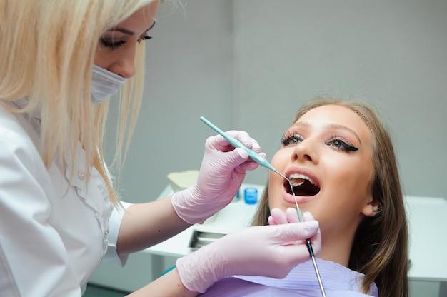 Arts in uniform controleren vrouwelijke patiënt tanden