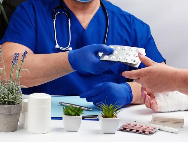 Arts in uniforme en blauwe latex medische handschoenen zit aan een tafel en onderzoekt een patiënt met een handletsel
