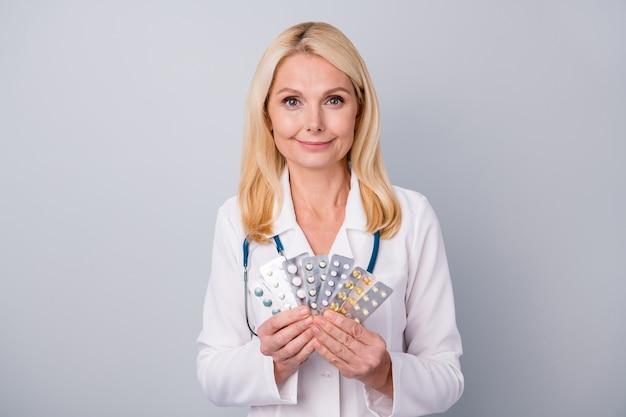 Arts in wit pak met een stethoscoop houdt pillen