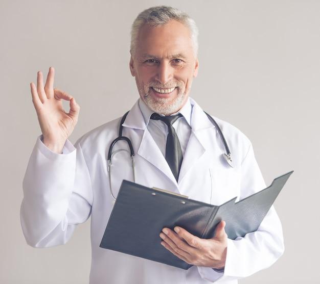 Arts in witte jas houdt een map en toont ok teken
