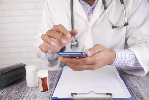 Arts in witte jas met behulp van een smartphone