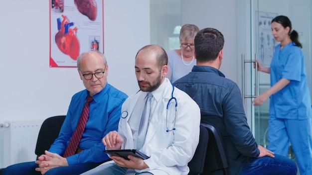 Arts in witte jas met stethoscoop diagnose bespreken met oude man in de wachtruimte van het ziekenhuis. verpleegkundige helpt senior vrouw met looprek. mens die op medisch onderzoek wacht.