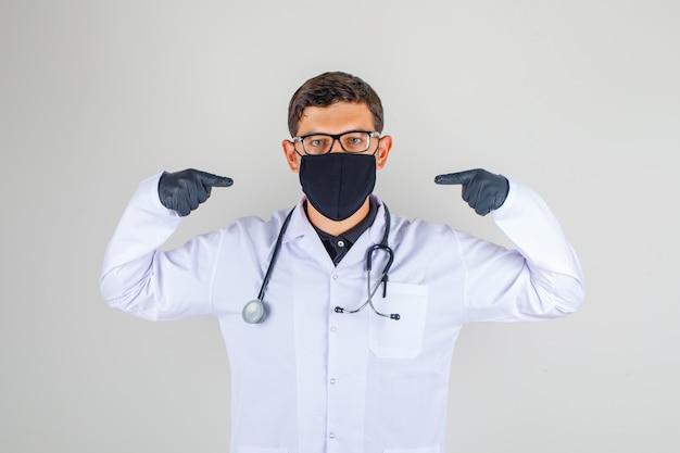 Arts in witte jas met stethoscoop wijst met vingers en kijkt trots